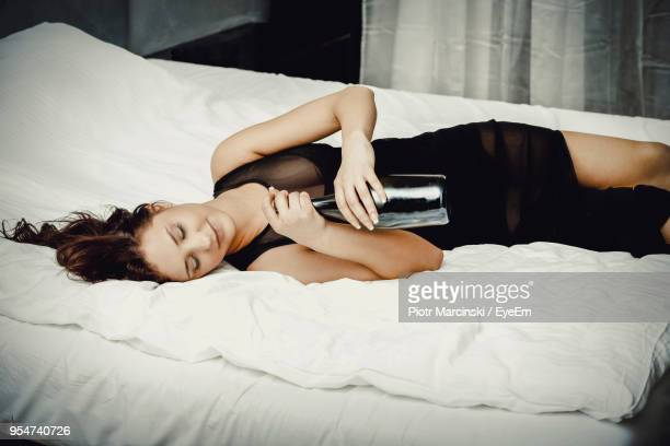 smiling young woman with wine bottle sleeping on bed at home - drunk woman stock pictures, royalty-free photos & images