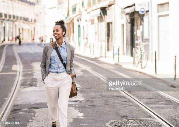 smiling young woman with wireless earphones in the city on the go, lissabon, portugal - crossbody bag stock pictures, royalty-free photos & images