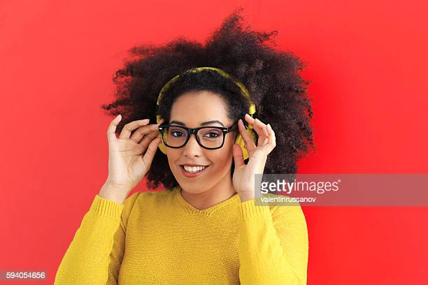 Smiling young woman with yellow headphones and eyeglasses