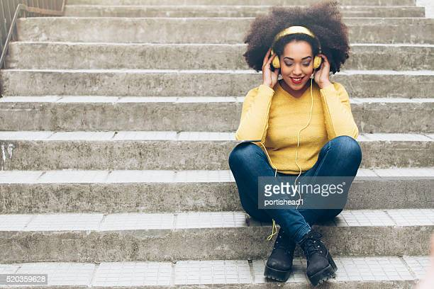 smiling young woman with yellow headphones sitting on stairs - city life stock pictures, royalty-free photos & images