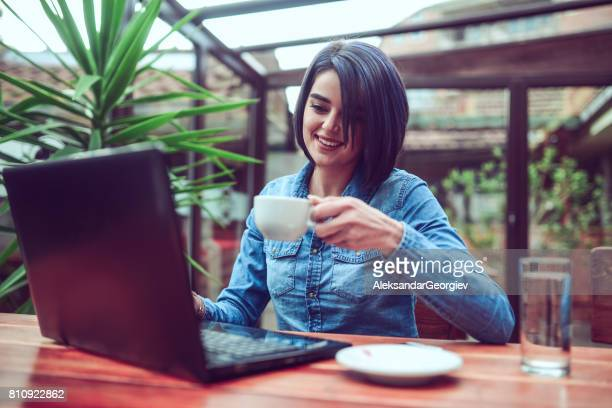 Smiling Young Woman Working with Laptop Computer in a Cafe