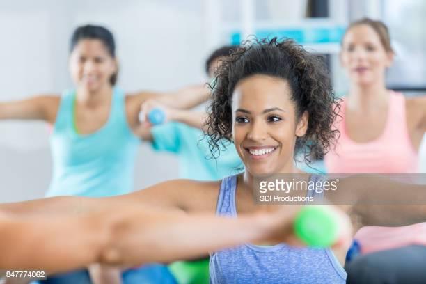Souriante jeune femme travaille bras dans la catégorie de poids formation exercice