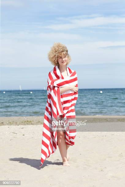 smiling young woman wrapped in beach towel standing in front of the sea - wrapped in a towel stock pictures, royalty-free photos & images