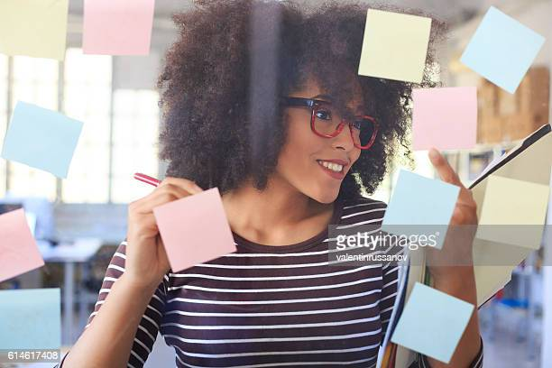 Smiling young woman writing on colorful reminders on glass wall