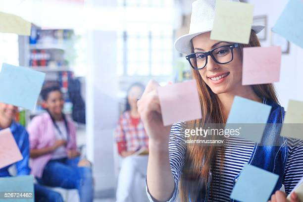 Smiling young woman writing on sticky notes