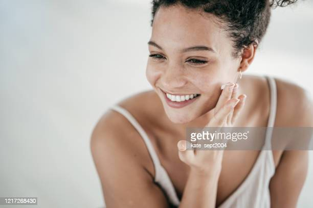 smiling young women applying moisturiser to her face - skin care stock pictures, royalty-free photos & images