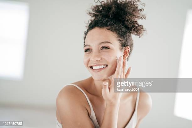 smiling young women applying moisturiser to her face - human skin stock pictures, royalty-free photos & images