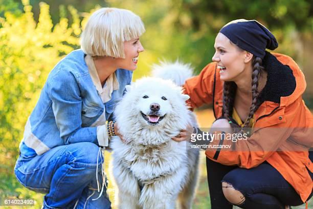 Smiling young women caressing a samoyed dog