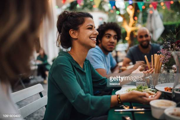 smiling young women gesturing while sitting with friends at table during dinner party - dinner party stock pictures, royalty-free photos & images