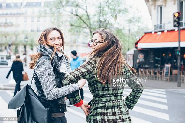 Souriant de jeunes femmes s'amusant et traverser la rue