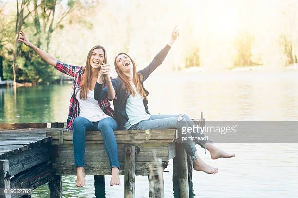 Smiling young women sitting on jetty and holding hands