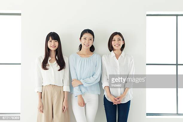 Smiling young women standing by wall
