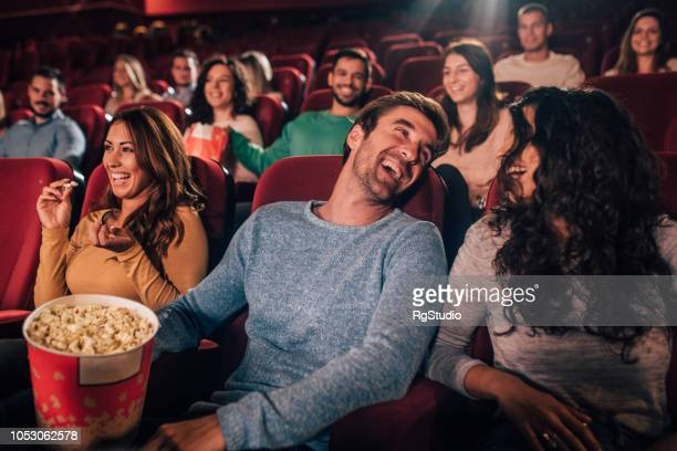 smiling youngsters at the cinema - comedy film stock photos and pictures