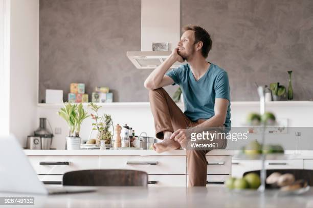 Smilingg man sitting on kitchen counter looking at distance