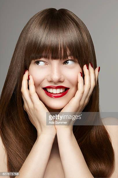 smilinh young woman with hands on her face