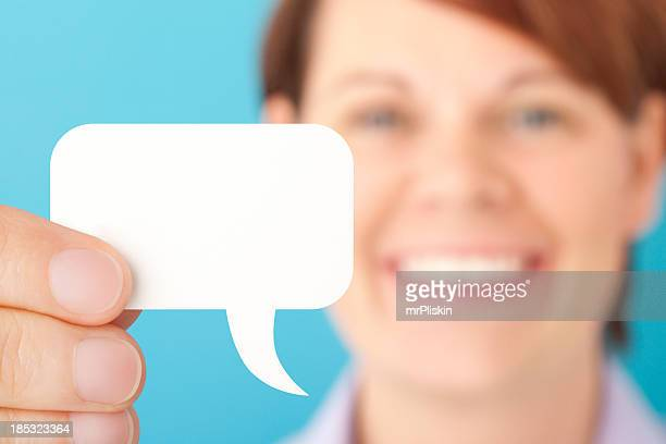 Smilng woman holding blank white speech bubble