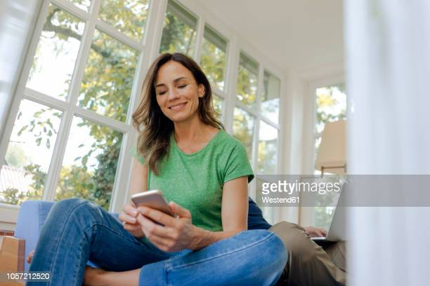 smilong mature woman sitting on couch at home using cell phone with man in background - ehefrau stock-fotos und bilder