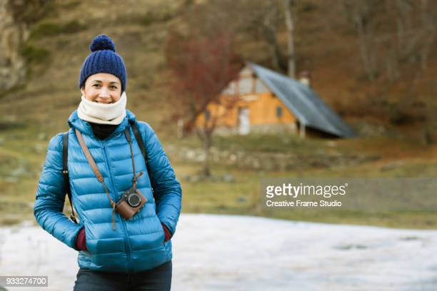 smily beautiful woman standing with his photo camera on a winter landscape with a log cabin on the background - jacke stock-fotos und bilder