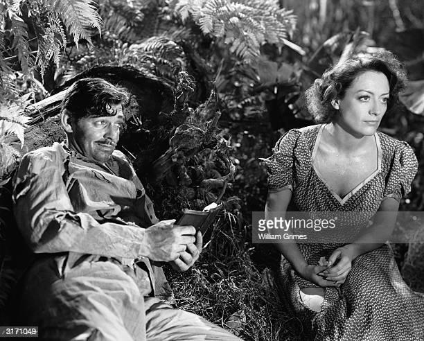 A smirking Clark Gable with Joan Crawford in a scene from Frank Borzage's prison escape drama 'Strange Cargo'