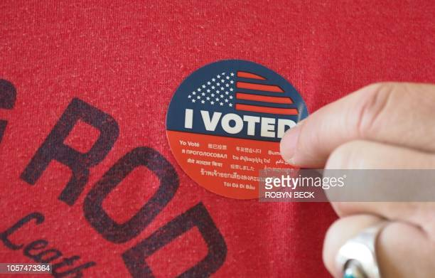 TJ Smith fixes an I Voted sticker on his shirt after basting his ballot at polling station during early voting for the midterm elections in the...