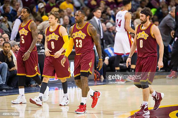 R Smith Matthew Dellavedova LeBron James and Kevin Love of the Cleveland Cavaliers walk to the bench during a timeout against the Miami Heat during...