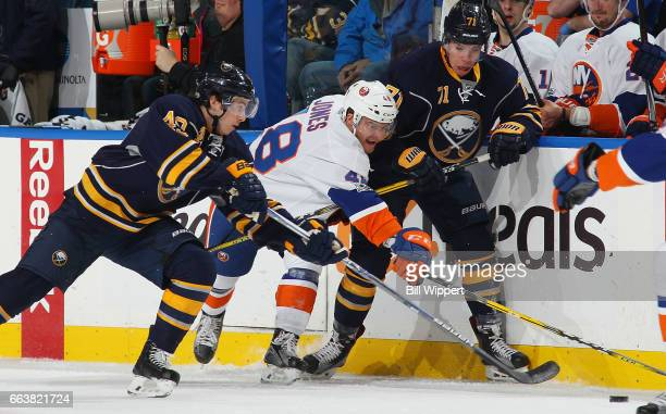 J Smith of the Buffalo Sabres and Connor Jones of the New York Islanders both playing in their first NHL games battle for the puck with Evan...