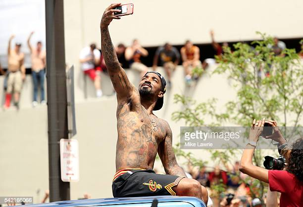 R Smith of the Cleveland Cavaliers takes a photo as the crowd cheers during the Cleveland Cavaliers 2016 NBA Championship victory parade and rally on...