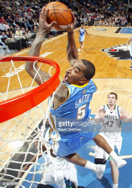 R Smith of the Denver Nuggets dunks against Corey Brewer and Kevin Love of the Minnesota Timberwolves during the game on March 10 2010 at the Target...