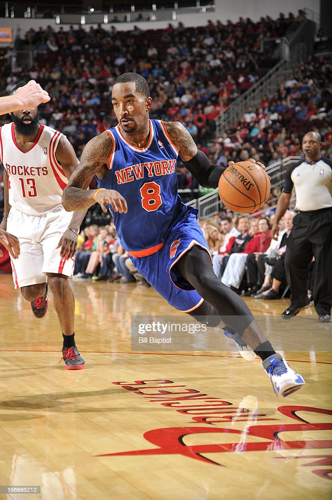 J.R. Smith #8 of the New York Knicks drives the ball against James Harden #13 of the Houston Rockets on November 23, 2012 at the Toyota Center in Houston, Texas.