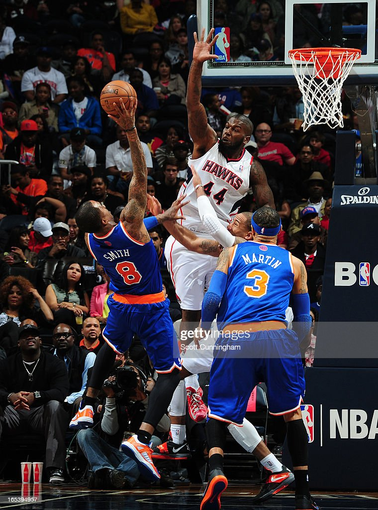 J.R. Smith #8 of the New York Knicks goes up for the shot against Ivan Johnson #44 of the Atlanta Hawks attempts to block it on April 3, 2013 at Philips Arena in Atlanta, Georgia.