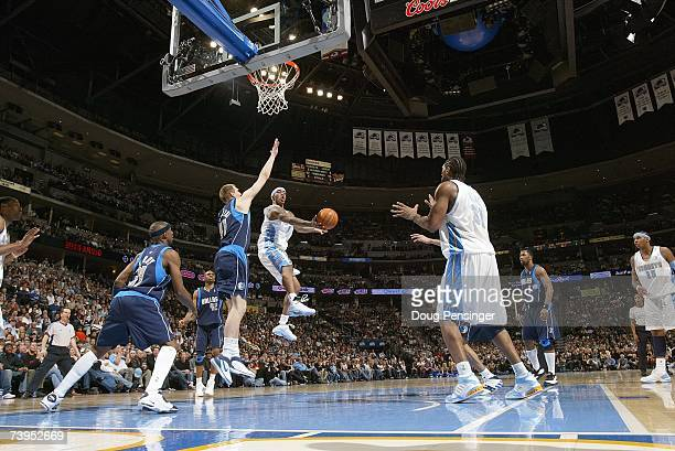R Smith passes to Nene of the Denver Nuggets during the NBA game against the Dallas Mavericks at the Pepsi Center on April 6 2007 in Denver Colorado...