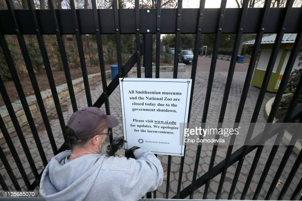 Smithsonian National Zoo employee removes a sign from the front gate telling visitors that the zoo is closed due to a government shutdown January 28,...
