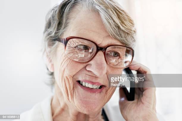 Smling alte Frau im Chat auf Handy