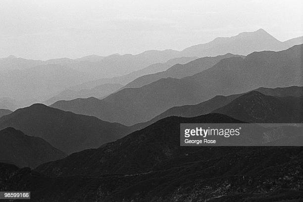Smog and smoke choke the San Gabriel Mountains above this city creating unique patterns along the ridges in this 1975 Claremont California photo