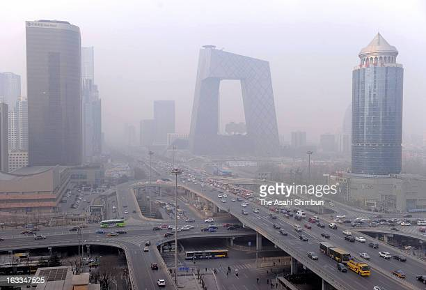 Smog casts over busy roads of central Beijing in the morning while China's air pollution concerns are voiced during the annual National People's...