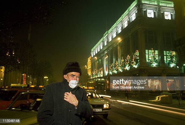 Smog caused by burning peat and coal fires pollutes the city centre of Dublin. Photo shows a man wears a face mask to protect his lungs against...