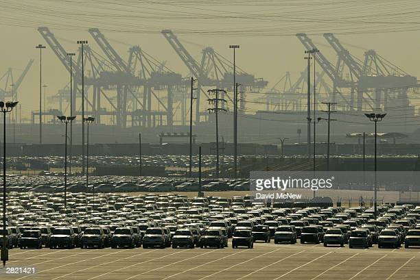 Smog envelopes cranes and newly imported cars in the shipyards of the Port of Long Beach December 18 2003 in Los Angeles California Weather...