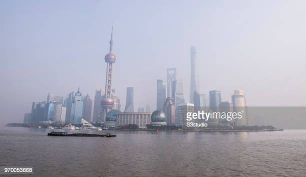 Smog hovers over the skyscrapers in Pudong including Oriental Pearl Tower Shanghai Tower Jin Mao Tower Pudong ShangriLa along the Huangpu river on...
