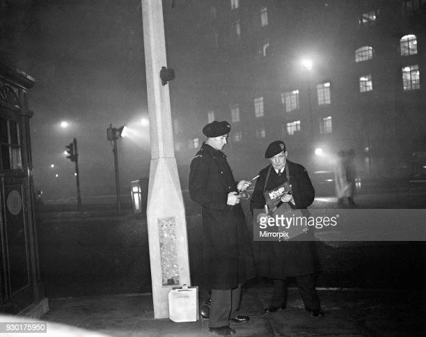 Smog wardens holding flares in thick fog in Central London, 5th January 1956.