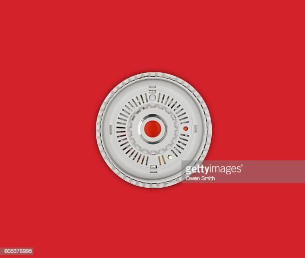 smoke alarm with red button on red background - romper el hielo fotografías e imágenes de stock