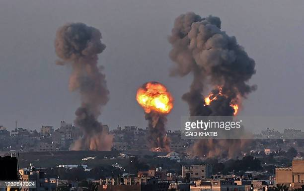 Smoke and a ball of fire rise above buildings in Khan Yunis in the southern Gaza Strip, during an Israeli air strike, on May 12, 2021. - Israeli air...