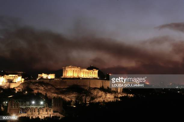 Smoke and blazes are seen in Athens behind the Acropolis as wildfires raged near the capital early on August 23 2009 Firefighters and local residents...