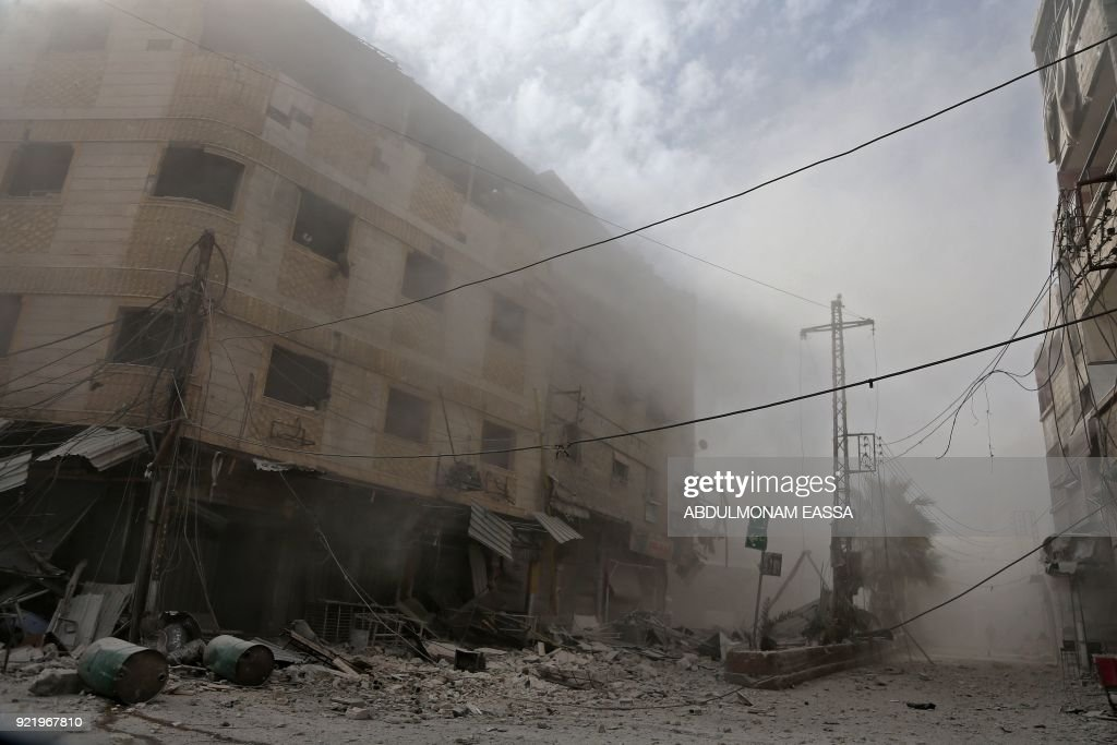 Smoke and dust are seen following a reported regime air strike in the rebel-held town of Hamouria, in the besieged Eastern Ghouta region on the outskirts of the capital Damascus on February 21, 2018. /