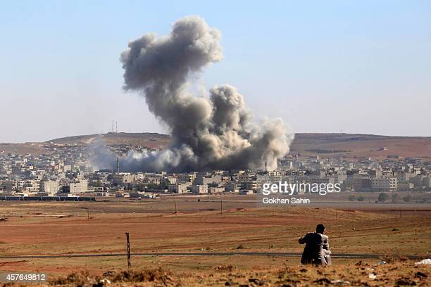 Smoke and dust rise over Syrian town of Kobani after an airstrike, as seen from the Mursitpinar crossing on the Turkish-Syrian border in the...