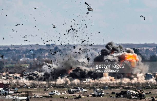 TOPSHOT Smoke and fire billow after shelling on the Islamic State group's last holdout of Baghouz in the eastern Syrian Deir Ezzor province on March...