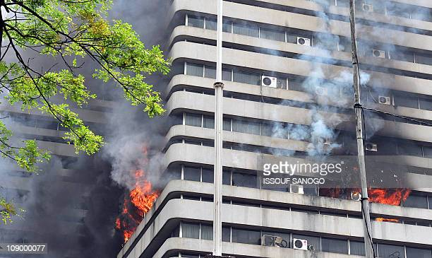 Smoke and fire come out the windows of the headquarters of the Ivorian National Treasury burning in the Plateau business district of Abidjan on...