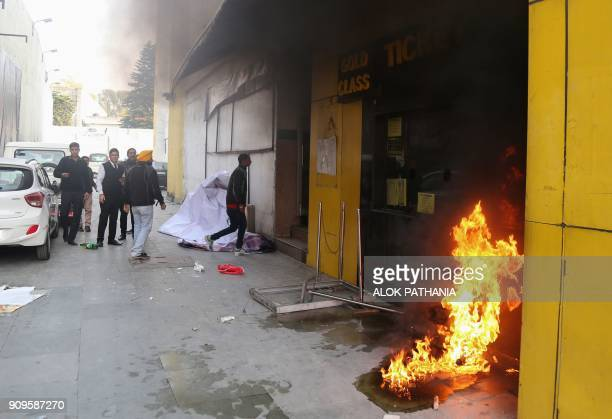 Smoke and fire emerges from a cinema ticket booth after an attack by activists in protest against the Bollywood film 'Padmaavat' in Jammu on January...