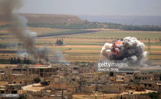 TOPSHOT Smoke and fire rise following reported Syrian government forces' bombardment on the town of Khan Sheikhun in the southern countryside of the...