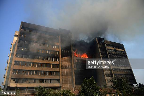 Smoke and flames billow from a burning garment factory in the key Bangladesh garment manufacturing hub of Gazipur on the outskirts of Dhaka on...