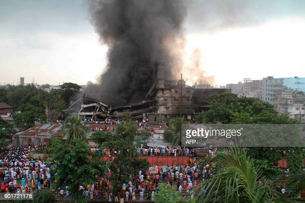 Smoke and flames billow from a burning garment factory in Tongi the key Bangladeshi garment manufacturing hub of Gazipur on the outskirts of Dhaka on...